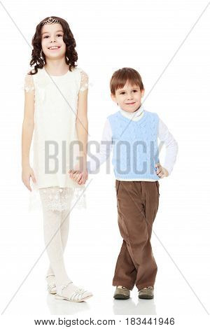 Beautiful little girl in a white dress holds the hand of his younger brother.Isolated on white background.