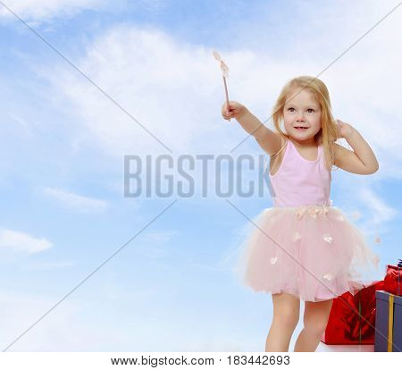 Adorable little Princess with a magic wand in the hands is surrounded by a beautifully Packed boxes with gifts. In the Christmas holiday. A girl waves a magic wand , she casts a magic spell.