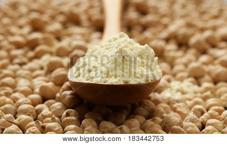 Natural organic chick pea flour in a wooden spoon