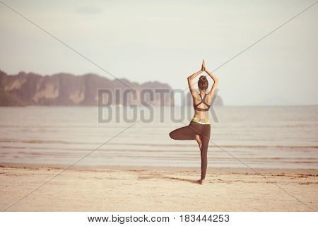 Yoga outdoors sporty fit woman doing hatha Vintage retro effect filtered hipster style image