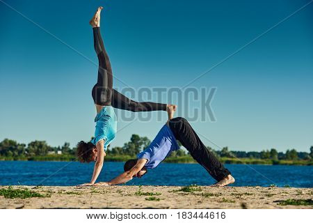 Young man and woman practicing acroyoga pose outdoors