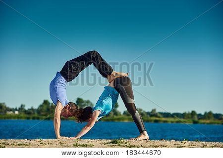 Couple practicing yoga together and doing Adhu Mukha Svanasana
