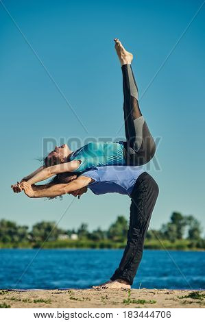 Relaxed sporty couple practicing acro yoga exercises