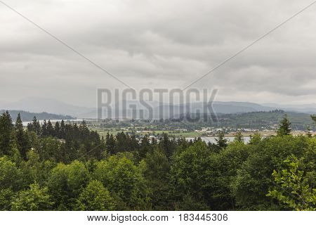 Trees water mountains and structures under cloudy sky in Astoria Oregon USA.
