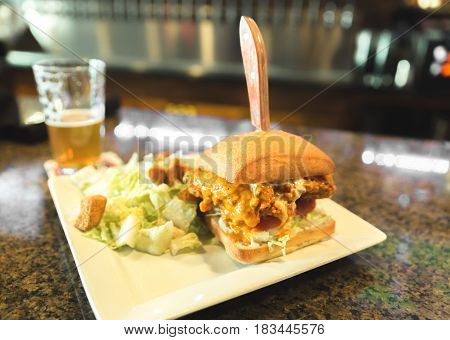 Fried chicken sandwich with salad on a bar in a brew pub.