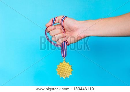 Hand holding a Gold medal with ribbon on a blue background.