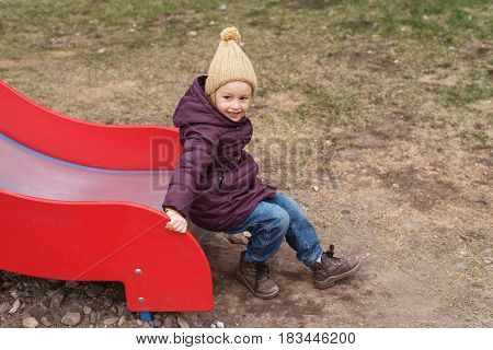 Little girl in a violet coat and a beige woolen hat in the playground.