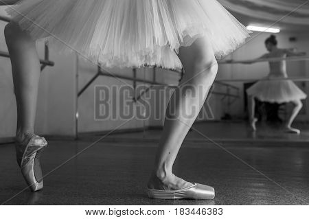 Ballet dancer in a pointe and a pack squats at the bench. Reflection in the mirror in the ballet class. Classical ballet. Prima ballerina. Shooting close-up. Black and white photography