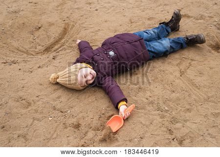 Little girl in a violet coat and a beige woolen hat lying on the sand in a sand-box with a plastic shovel in her hand.