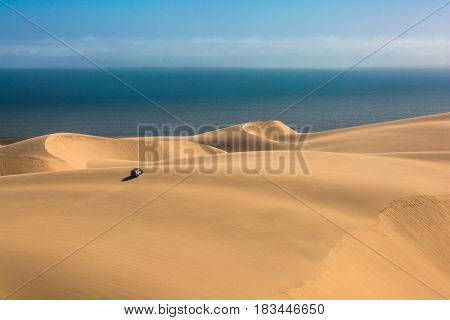 Gorgeous and dangerous jeep - safari through the huge sand dunes on the ocean coast. The concept of exotic and extreme tourism. Atlantic coast of Namibia, south of Africa