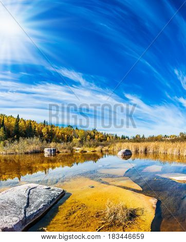 Indian summer in Manitoba, Canada. Wonderful autumn day. Cirrus clouds are reflected in the Winnipeg River. Old Pinawa Dam Park. The concept of ecological and recreational tourism
