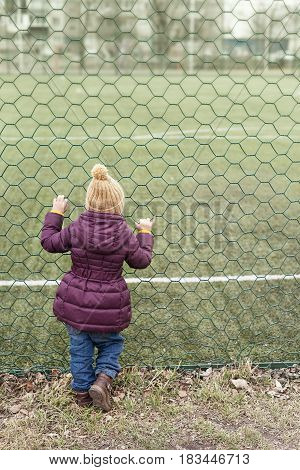 Little girl in a violet coat and a beige woolen hat looking at the playing-field through a green grate.