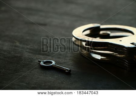 Old handcuffs on old wooden table background