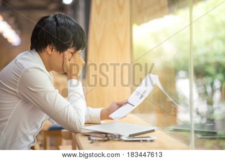 frustrated stressed business man checking chart and diagram report paper in workplace young Asian entrepreneur fail in result and worried about deadline of job risk management concepts