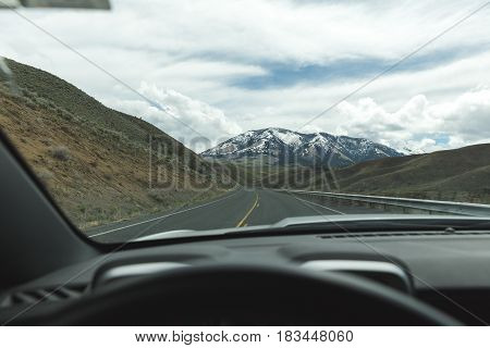 Driver perspective on highway with view of snowcapped mountain and cloudy sky.