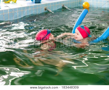 Elementary age girl helping her little sister  to swim in a seawater swimming pool