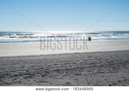 Couple in the distance walking along the shoreline on a beach in Florida