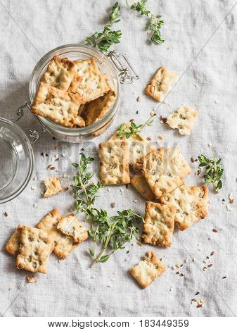 Salty sunflower seeds and thyme crackers on a light table top view. Delicious snack