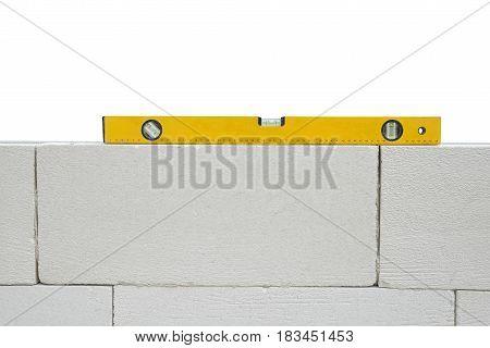 Yellow spirit level on white brick wall.