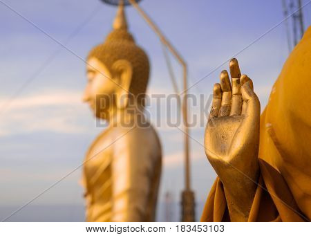 Golden Buddha and hand of praying buddhist monk's statue TIger Cave Temple Krabi Province Thailand. Focus on the hand.