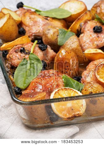 Close up view of chicken thighs with potatoes, lemon and black olives, cooked in oven on gray concrete background. Baked chicken leg quarter in heat-proof glass.