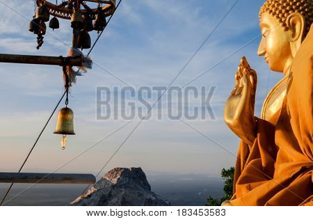 Blessing hand of praying buddhist monk's statue and big golden buddha at the backgroundб TIger Cave Temple, Krabi province, Thailand. Focus on the foreground hand.