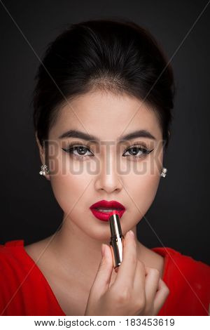Professional Make-up. Attractive Asian Model Applying Red Lipstick.