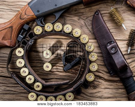 Hunting equipment - pump action shotgun, 12 gauge cartridge and hunting knife on the wooden table.