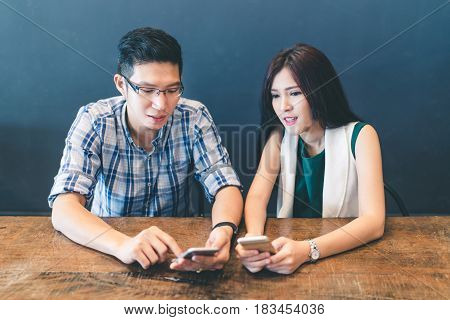 Young Asian couple college students or coworkers using smartphone together at cafe modern lifestyle with gadget technology or love and relationship concept