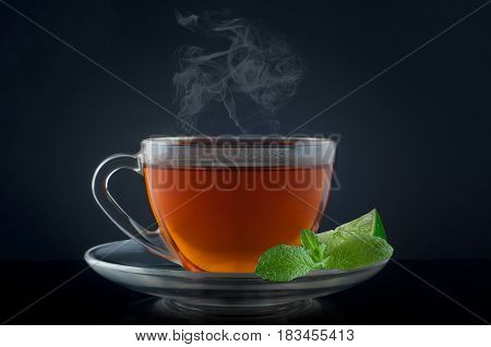 Cup tea with mint and lime on a black background.
