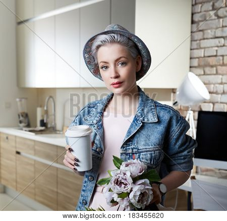 Portrait of attractive young woman arriving at home drinking coffee.