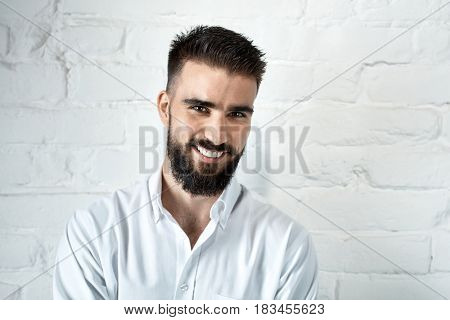 Portrait of happy bearded man smiling in front of white brick wall.