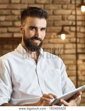 Happy bearded man using tablet at trendy home smiling, looking at camera.