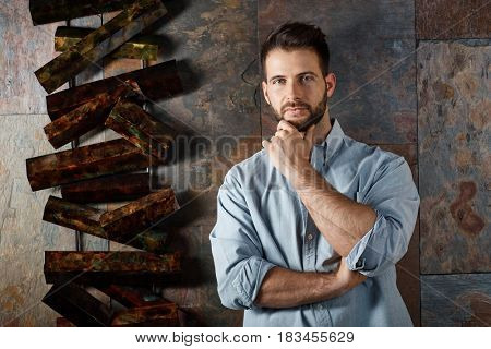 Portrait of handsome bearded man looking at camera with serious facial expression.