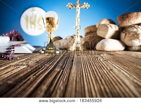 First Holy Communion. Catholic religion theme. Crucifix, Bible, bread on rustic wooden table and blue background.