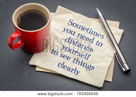 Sometimes you need to distance yourself to see things clearly - handwriting on a napkin with cup of coffee against gray slate stone background
