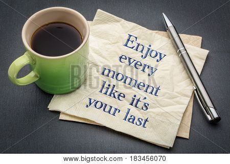 Enjoy every moment like it is your last - handwriting on a napkin with cup of coffee against gray slate stone background