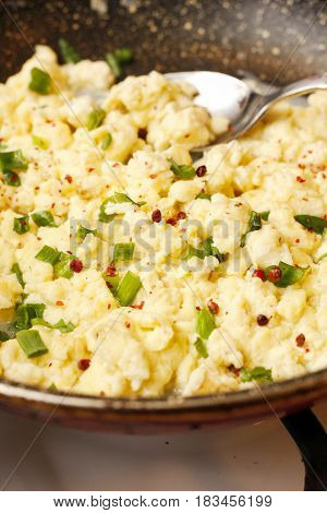 Scrambled Eggs With Onion In Black Pan