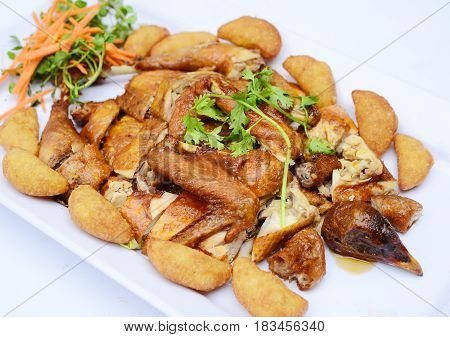 Chopped Fried Chicken With Potatoes And Herbs On White Platter