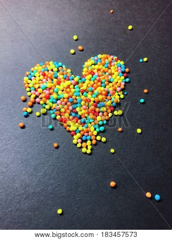 Figure from confectionery sprinkling colored balls. Abstract sweet multi colored background on black backdrop