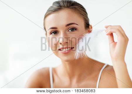 people and beauty concept - beautiful woman with feather touching her face skin at home bedroom