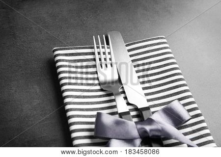 Table setting with silver cutlery in striped napkin on grunge background