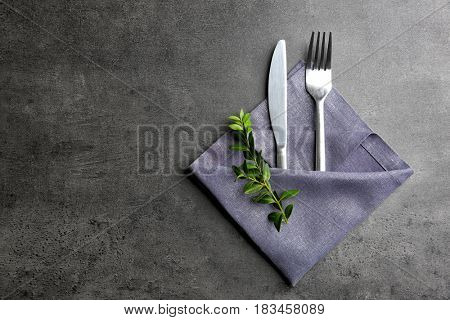 Table setting with silver cutlery in napkin on grunge background