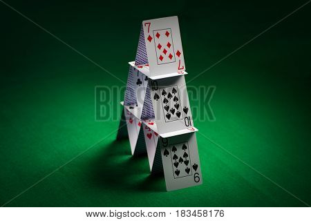 casino, gambling, games of chance, hazard and insecurity concept - house of playing cards on green table cloth