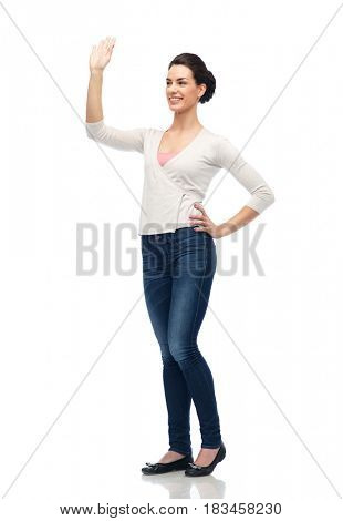 gesture, fashion, portrait and people concept - happy smiling young woman in cardigan cardigan and jeans hand over white