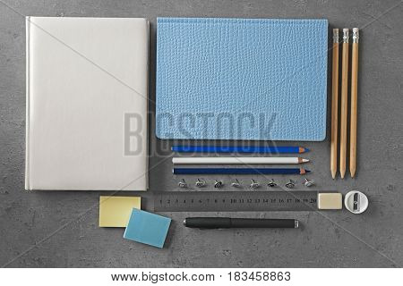 Notebooks and different stationery on color background