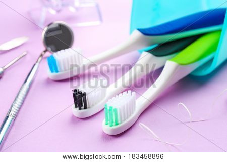 Toothbrushes, dental instruments and floss on color background