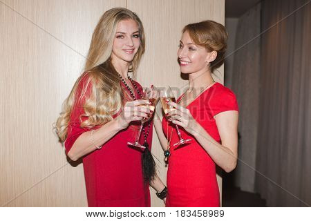 Two cheerful women in red dress clanging the glasses with champagne. Horizontal indoors shot.