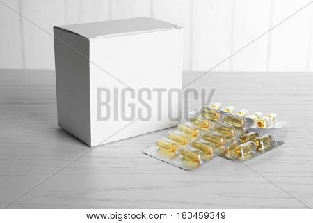 Blister packages of fish oil capsules and white carton box on wooden table