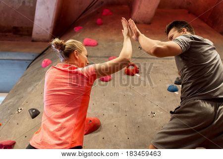 fitness, extreme sport, bouldering, people and healthy lifestyle concept - man and woman exercising at indoor climbing gym and making high five gesture